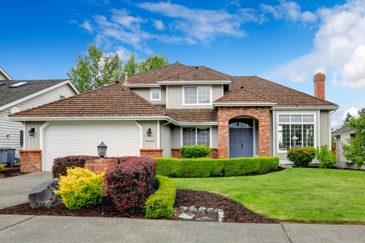 classic-house-exterior-with-brick-trimmed-entrance-porch-green-lawn-and-trimmed-hedges-garage
